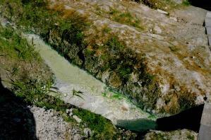 廃湯で緑色の川ができている