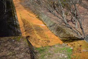 道の横にある川は成分で赤茶色